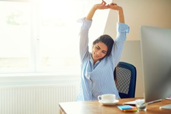 Grinning young woman in blue long sleeve shirt stretching in front of desk at home
