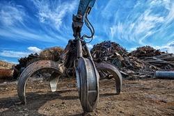 Gripper excavator on a scrap yard. HDR - high dynamic range