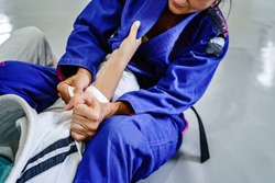Grips from the guard in brazilian jiu jitsu bjj or judo training sparring two female women athletes fighters drilling techniques for the competition advanced guard holding kimono gi for self-defense