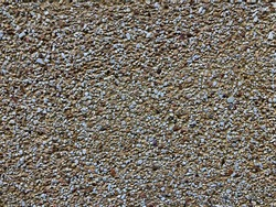 Grit gravel small wall texture. Brown gritty background. Exterior concrete wall with gravel small surface.
