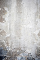 Gritty grungy background of distressed and peeling faded concrete wall