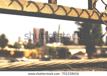 Gritty rustic image a blurred Downtown Skyline from the Overpass of I-101 with  Chain-link fence in the Foreground