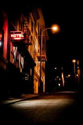 Gritty Urban alley way with hotel sign lit in neon - Noir look,,