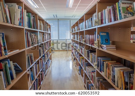 GRIZE, SLOVENIA - 26. september 2016 Many shelves with different books in a school library. It looks very spacious and beautiful.