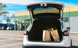 Groceries from a supermarket in a car trunk. Social distancing. Food delivery during quarantine. Paper eco bags for shopping
