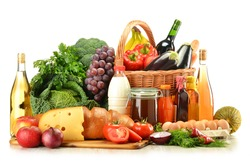 Groceries in wicker basket including vegetables, fruits, bakery and dairy products and wine isolated on white. Balanced diet