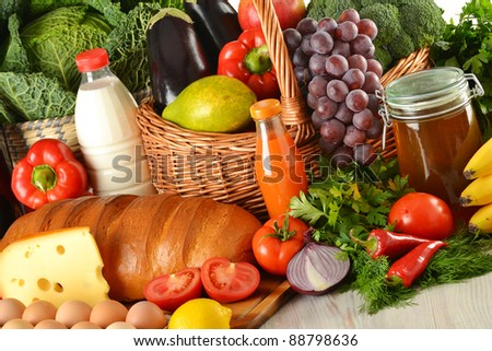 Groceries in wicker basket including vegetables, fruits, bakery and dairy products and wine