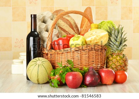 Groceries in wicker basket on kitchen table including vegetables, fruits, bakery and dairy products and wine