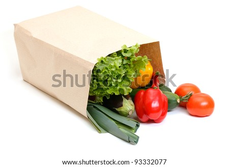 grocery bag full of vegetables isolated on white background