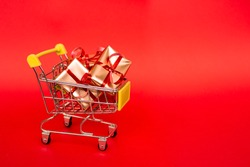 Grocery basket with golden gift boxes with red ribbon on red background banner with copy space. Christmas shopping online. Winter holiday sales, seasonal sales, Black Friday, Christmas, discounts and
