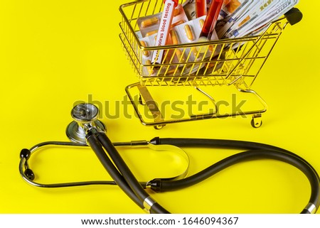 Grocery cart with COVID 2019. Corona virus outbreaking medicines tablets and currency US dollar banknotesin shopping carts on stethoscopes
