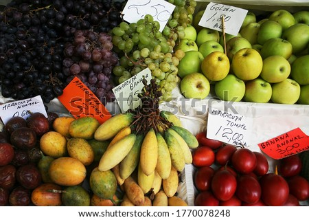 Grocery market with colorful exotic fruits. Text: golden - apple variety, passion fruit normal, passion fruit pineapple, passion fruit banana, passion fruit tomato, banana pineapple.