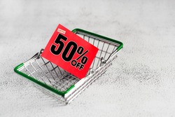 Grocery mini shopping basket with red card with fifty percent discount sign, closeup. Conceptual image of clearance sale, seasonal discounts in shopping stores, black friday