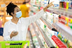 Grocery Shopping. African American Woman Wearing Protective Face Mask In Supermarket, Buying Food Products In Groceries Store Indoor. Female Buyer With Shop Cart In Hypermarket