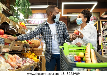 Grocery Shopping. African Family Couple In Masks Buying Vegetables Together Standing With Shop Cart In Supermarket Groceries Store Indoor. Buyers Choosing Healthy Food Concept