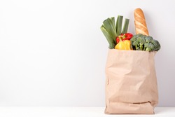 Grocery shopping bag with food on grey background
