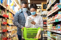 Grocery Shopping. Black Couple Wearing Face Masks In Supermarket, Buying Groceries With Checklist, Walking With Trolley In Food Store Indoors. Customers Buy Essentials During Virus Pandemic Outbreak