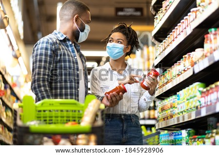 Grocery Shopping. Black Family Couple In Masks Buying Groceries In Supermarket Store Indoors. Buyers Standing With Shopping Cart In Aisles Choosing Food Products. Shop Safe During Covid-19 Pandemic