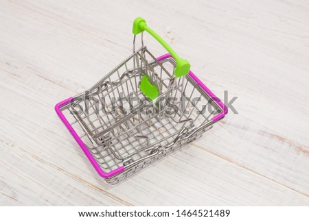 Grocery shopping cart and cart on a wooden background. #1464521489