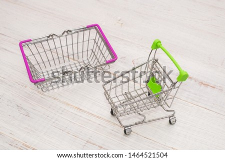 Grocery shopping cart and cart on a wooden background. #1464521504