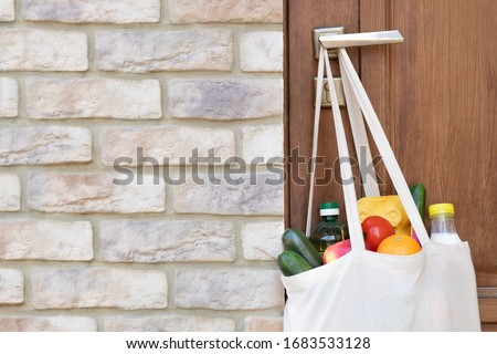 Grocery shopping in a bag hanging on door handle during a quarantine