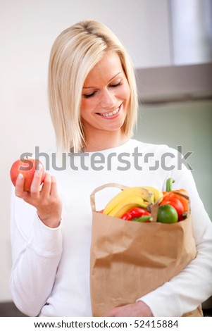 Grocery shopping woman taking out her purchases from a paper bag