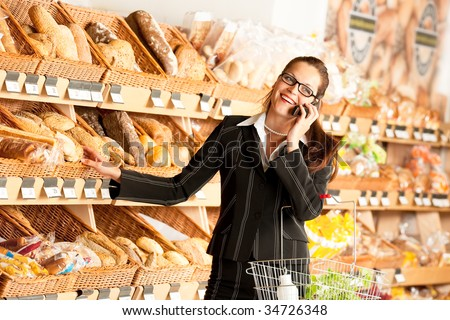 Grocery store: Business woman with mobile phone in a supermarket