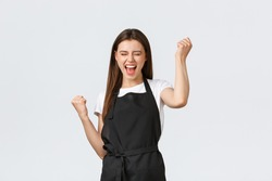 Grocery store employees, small business and coffee shops concept. Excited happy cafe worker celebrating great news. Cheerful thrilled barista dancing from happiness and rejoice