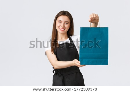 Grocery store employees, small business and coffee shops concept. Friendly helpful, smiling saleswoman handing over customer their bag with purchase, clerk or cashier processing order