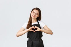 Grocery store employees, small business and coffee shops concept. Lovely friendly-looking barista inviting have taste of new drinks in cafe, showing heart sign to express love for visitors