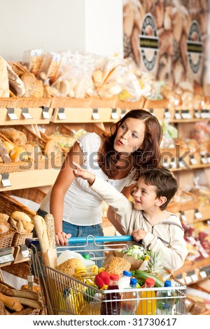 Grocery store - Mother with child in a supermarket - stock photo