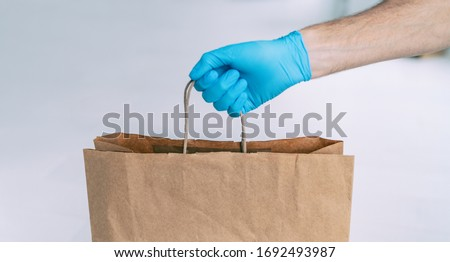 Grocery store shopping delivery man giving paper bag wearing blue glove as protection for COVID-19 Coronavirus precautions.
