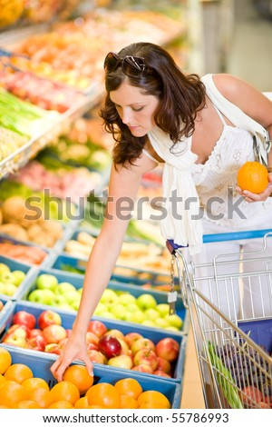 Grocery store - smiling woman shopping with trolley in supermarket, holding orange - stock photo