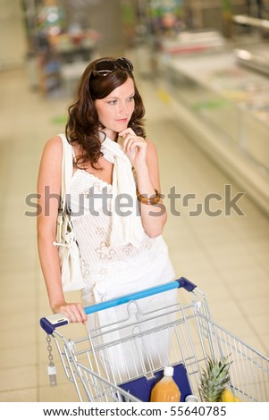 Grocery store - thoughtful woman shopping with trolley in supermarket