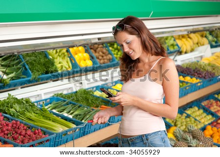 Grocery store - Woman holding mobile phone in a supermarket