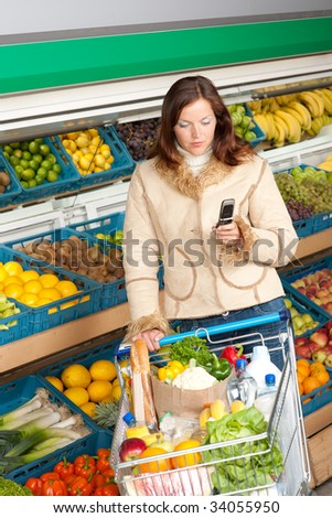 Grocery store - Woman in winter outfit with mobile phone