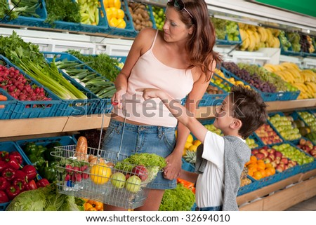 Grocery store - Woman with child buying vegetable in a supermarket
