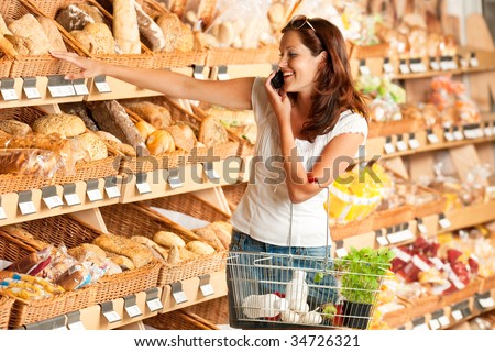 Grocery store: Young woman holding mobile phone and shopping basket