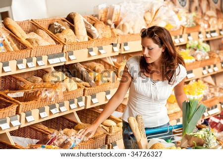 Grocery store: Young woman with shopping cart and choosing bread