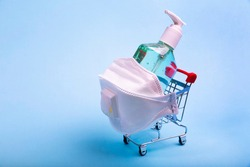 Grocery supermarket trolley cart with respirator and a bottle of alcohol hand gel sanitizer. Coronavirus shopping concept on blue background.