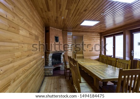 GRODNO, BELARUS -  AUGUST 2019: Interior of the kitchen and banquet hall in  living guest room with oak table in wooden vacation eco house with fireplace #1494184475