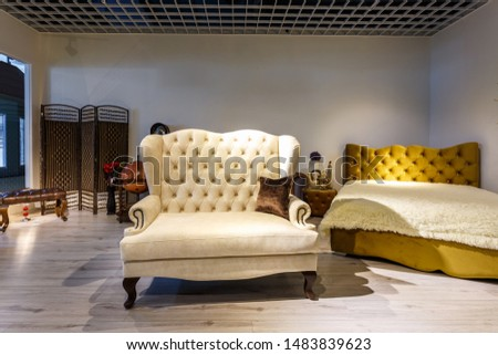 GRODNO, BELARUS - DECEMBER 2018: white milk bench and white bed in chester style for elite loft interior in expensive store showroom of furniture #1483839623