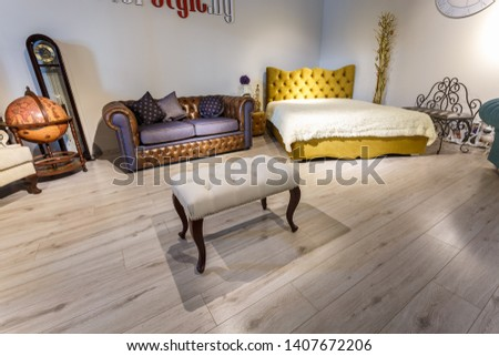 GRODNO, BELARUS - DECEMBER 2018: yellow leather bed and white bench in chester style for elite loft interior in expensive store showroom of furniture #1407672206