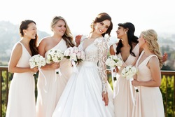 Grogeous dark-haired bride in luxurious dress looks at bridesmaids admiring her
