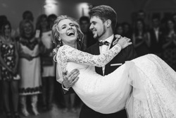 Groom admires happy bride laughing in his arms