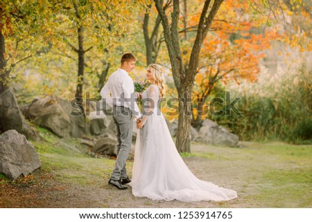 groom affectionately looks at the bride in a gray steep wedding expensive dress with a long train, gently holds her hand, stand together in forest with green and orange trees, gentle sensual photo #1253914765