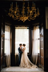 Groom almost kisses bride against the background of the large windows of the old villa. View from the next room with a chandelier with candlesticks on the ceiling. Lake Como