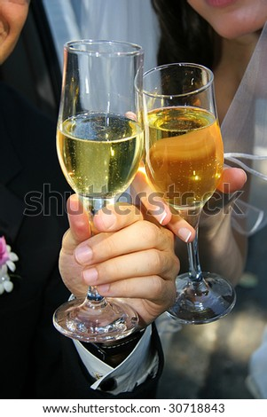 Groom and Bride hold glasses of champagne