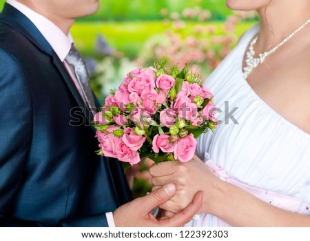 groom and bride holding bouquet of tiny roses