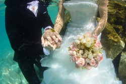 groom and bride holding hands and wedding bouquet underwater